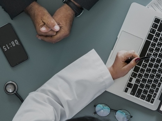 doctor pointing to laptop in front of patient with hands folded