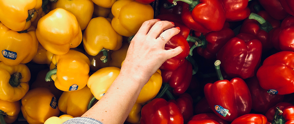 hand reaching between yellow and red peppers