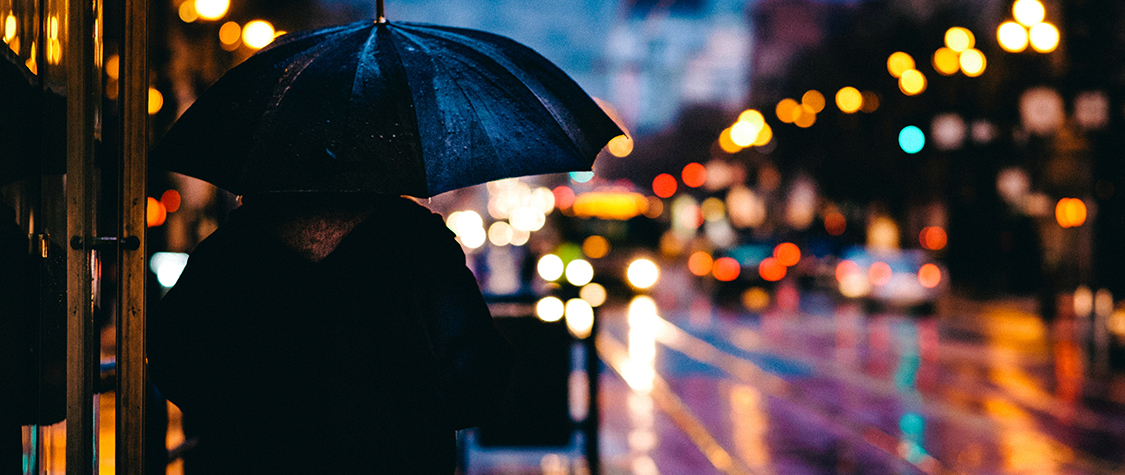 person holding umbrella near street on rainy night