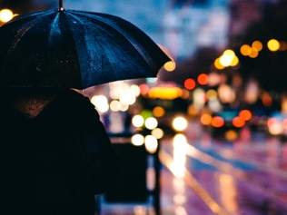 person holding umbrella near street on rainy night