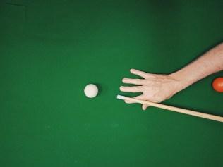 man holding pool cue, preparing to strike cue ball