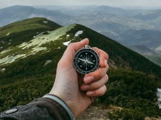 hand holding compass atop mountain ridge