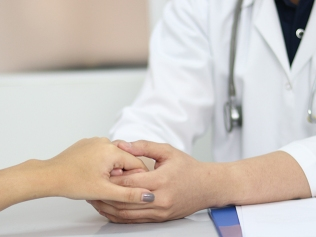 doctor holding hands with patient