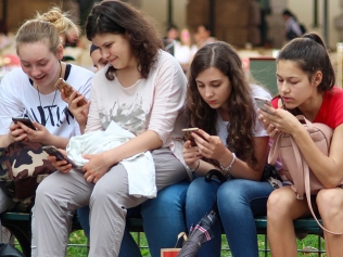 girls sitting on bench using their phones