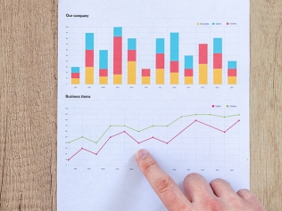 finger pointing at business bar graphs