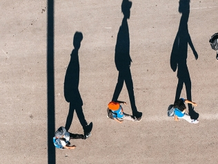 people with shadows walking on street