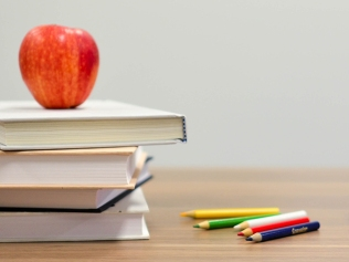 apple atop stack of books, alongside pencils and ABC blocks
