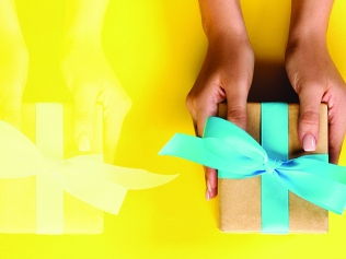 two pairs of hands, one transparent, handing gifts forward against a yellow background
