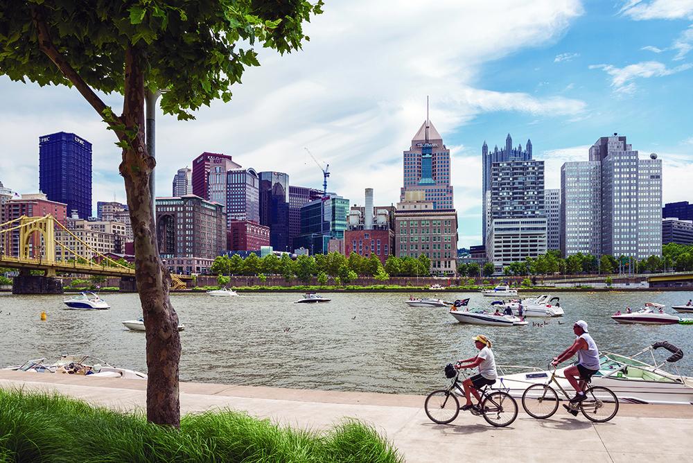 bikers biking along river in Pittsburgh