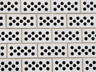a pattern of white bricks with circular black holes throughout
