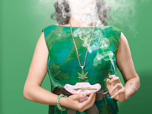 woman in green with marijuana smoke obscuring her face