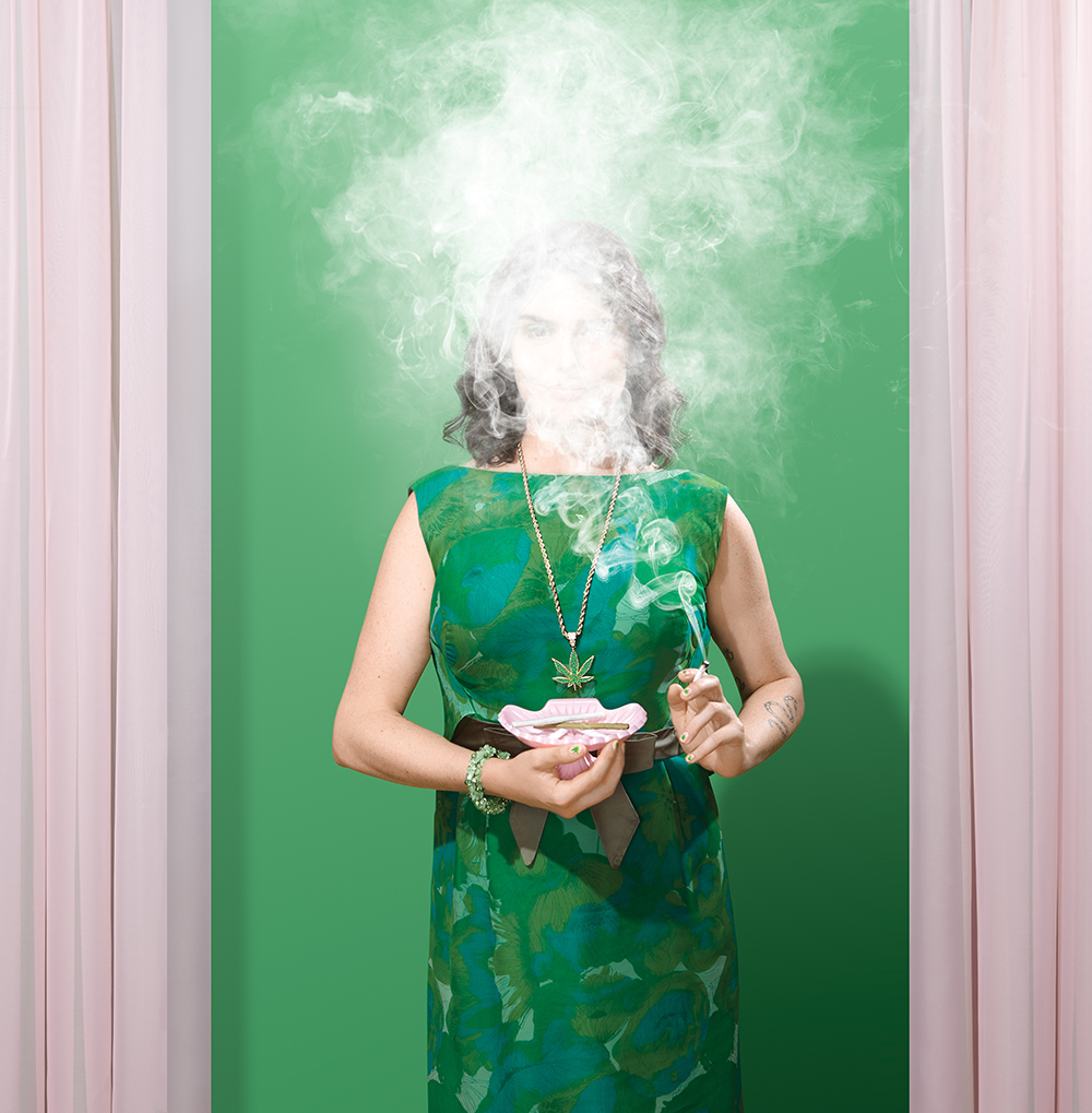 woman wearing green dress against green background with face obscured by marijuana smoke
