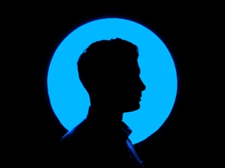silhouetted profile of man's head against blue circle
