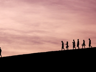 silhouetted figures walking down a hill at sunset