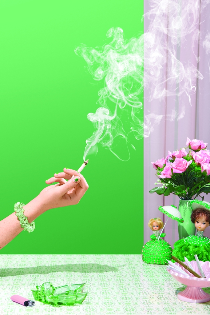 woman's hand holding lit marijuana joint