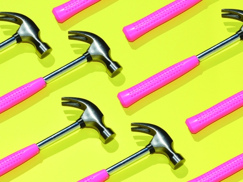 pattern of hammers with pink handles against yellow background