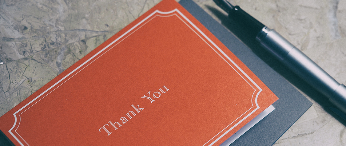 red 'thank you' card next to fountain pen