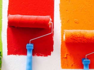 green, red, orange and blue paint rollers on white wall