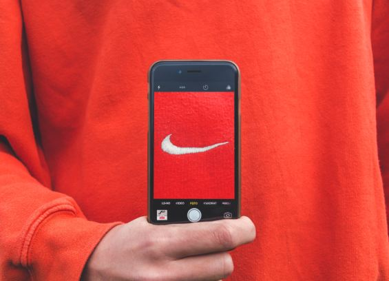 What is a trademark? Person holding iPhone taking picture of Nike label.  Nike is a trademarked symbol.