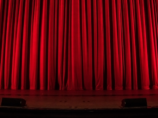 closed red curtain on stage