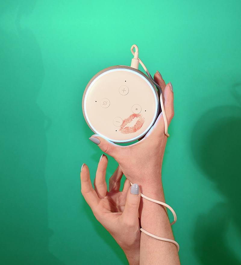 woman's hands holding amazon echo speaker with lipstick stain against green background