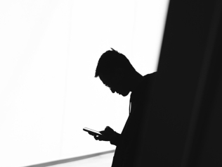 black and white photo with silhouetted man checking phone