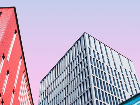 three multicolored buildings against purple sky