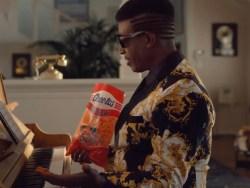 MC Hammer seated at piano holding bag of Cheetos