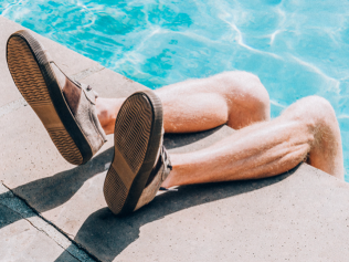 man's feet hanging over side of swimming pool