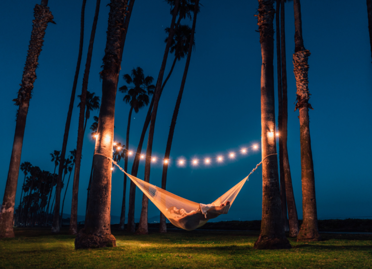couple in hammock at night underneath palm trees