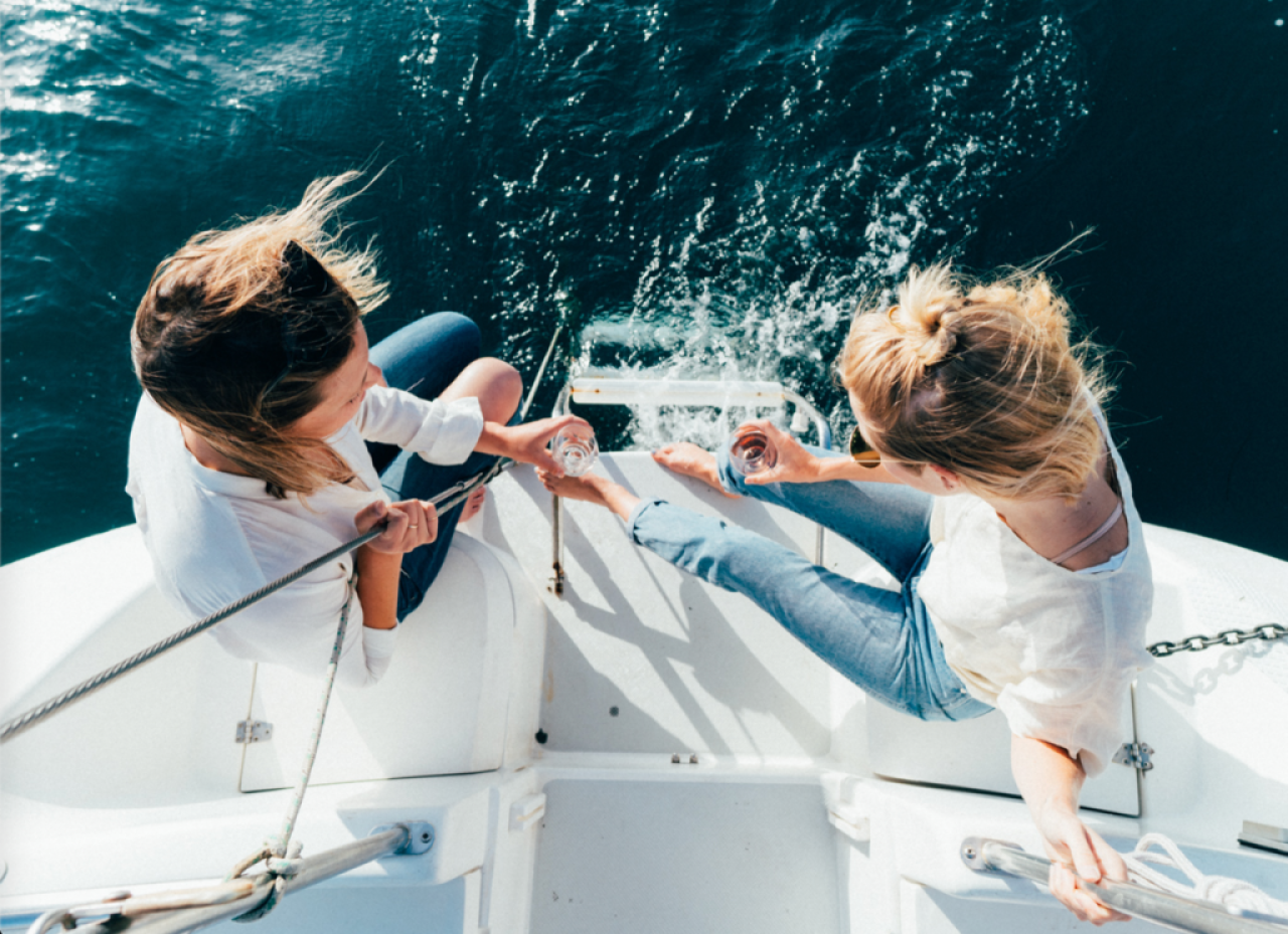 overhead view of two women standing on edge of sailboat