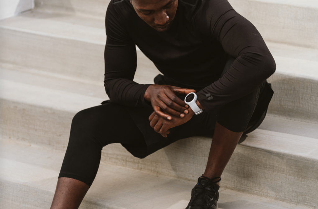 man in athletic wear sitting and checking watch