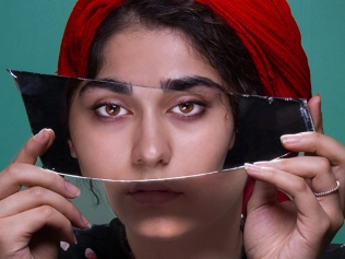 woman holding shard of mirror in front of her face