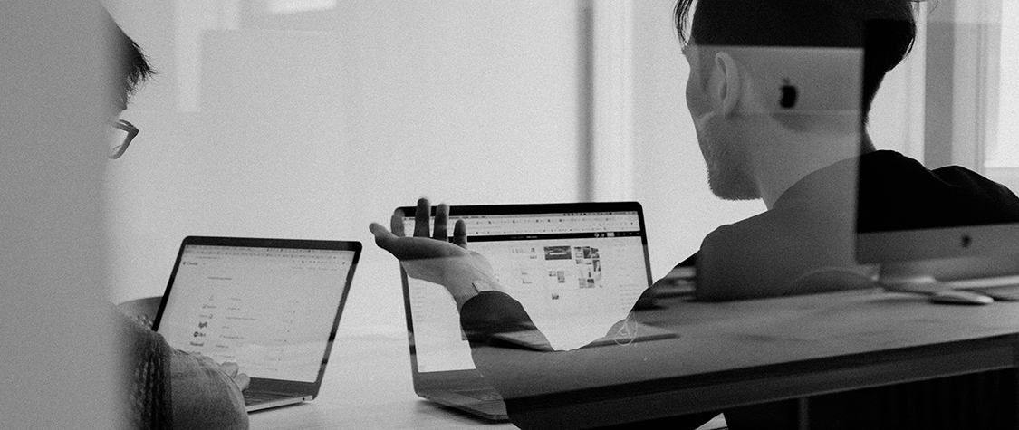 black and white photo of two people on laptop, one man with arm raised inquisitively