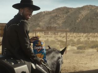 Lil Nas X seated on horse holding bag of Doritos chips