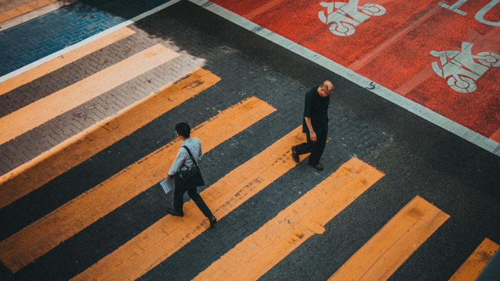 2 men walking different directions on a crosswalk