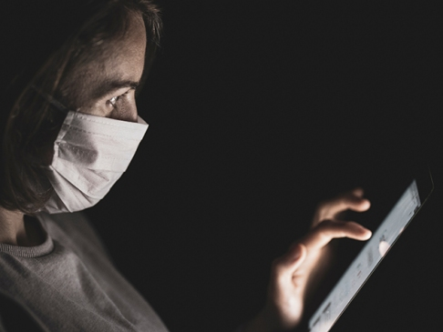 woman wearing mask using smart phone