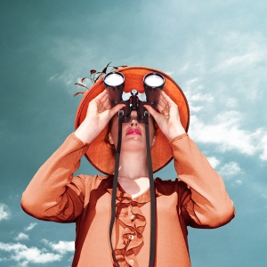 woman wearing hat looking through binoculars