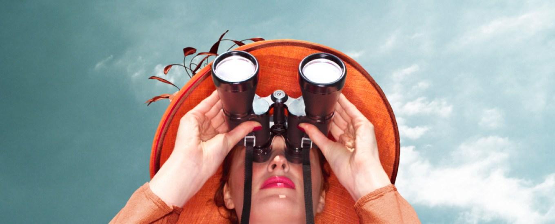 woman wearing hat looking through binoculars