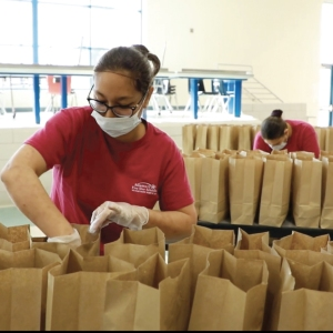 women in red shirts wearing face masks bagging brown bags
