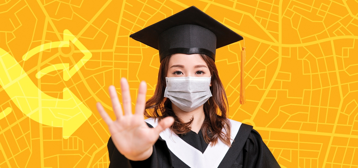 woman holding up hand wearing graduation robes