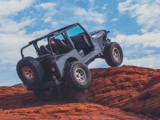 jeep driving up red rocks