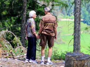 two elderly people standing in a forest