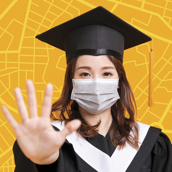 masked woman wearing graduation garb holding up hand