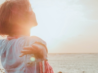 woman on beach with outstretched arms facing sun