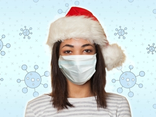 masked woman wearing Santa hat in front of snowflake background