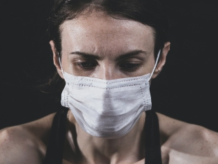 anxious woman wearing mask with face lowered