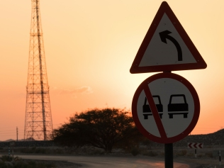 road warning sign with sunset in background
