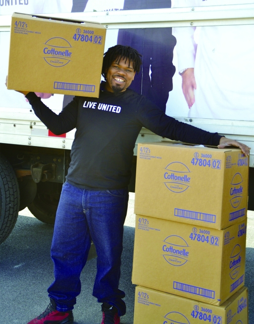 smiling man with boxes of cottonelle toilet paper