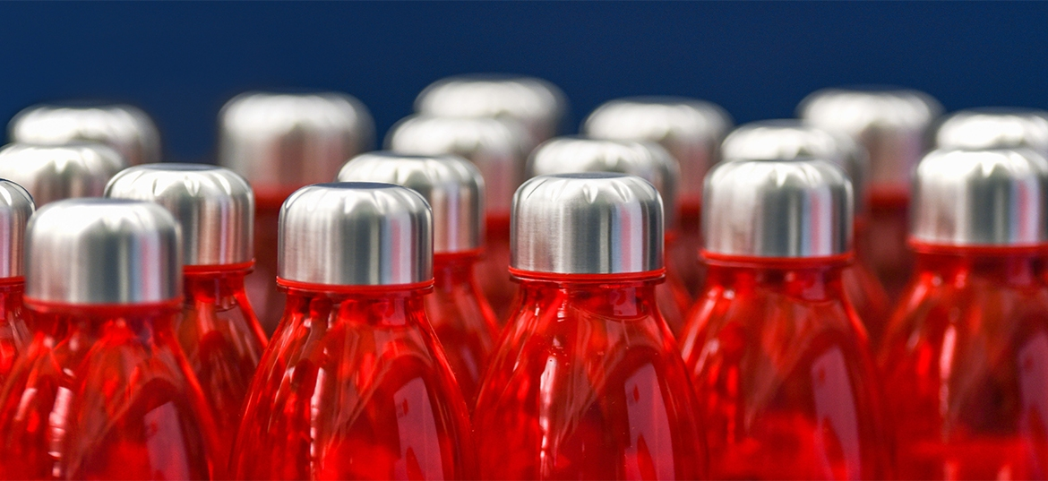 Red water bottles with silver metallic caps in rows isolated on